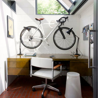 This is an example of an industrial home office and library in Hampshire with brick flooring.