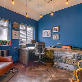 Inspiration for an industrial home office and library in Hertfordshire with blue walls, dark hardwood flooring, a built-in desk and brown floors.