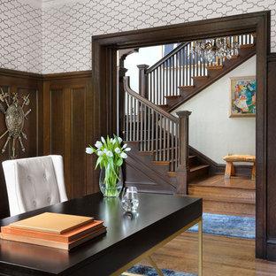 セントルイスの広いトラディショナルスタイルのおしゃれなホームオフィス・書斎 (ライブラリー、青い壁、濃色無垢フローリング、標準型暖炉、木材の暖炉まわり、自立型机、茶色い床) の写真