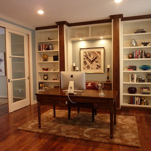 Example of a mid-sized arts and crafts freestanding desk medium tone wood floor study room design in Minneapolis with blue walls