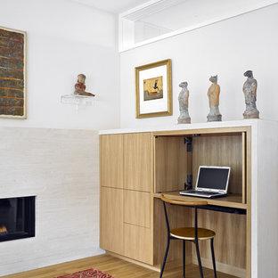 サンフランシスコの中くらいのモダンスタイルのおしゃれなホームオフィス・書斎 (造り付け机、白い壁、横長型暖炉、無垢フローリング) の写真
