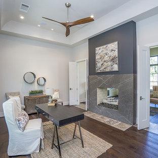 Idées déco pour un grand bureau scandinave avec un mur gris, un sol en bois foncé, une cheminée standard, un manteau de cheminée en pierre, un bureau indépendant et un sol marron.