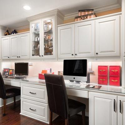 Mid-sized elegant built-in desk medium tone wood floor and brown floor study room photo in Columbus with beige walls
