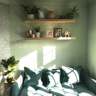 Modelo de despacho escandinavo, pequeño, con paredes verdes, suelo de madera en tonos medios, chimenea de esquina, marco de chimenea de ladrillo y escritorio empotrado