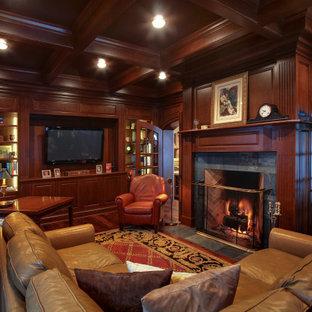 Inspiration för stora klassiska hemmabibliotek, med mörkt trägolv, en standard öppen spis, en spiselkrans i sten och ett fristående skrivbord