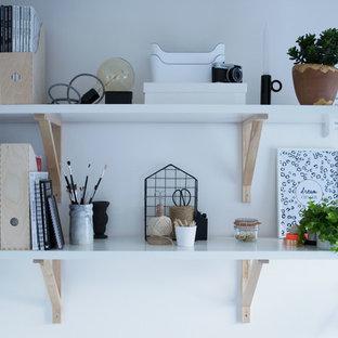 Bild på ett litet nordiskt hemmabibliotek, med vita väggar, heltäckningsmatta och ett fristående skrivbord