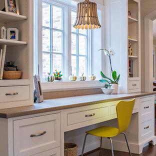 Diseño de despacho tradicional con paredes blancas, suelo de madera en tonos medios y escritorio empotrado