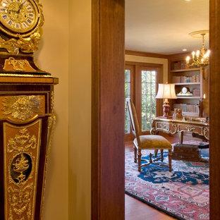 Immagine di un ufficio vittoriano di medie dimensioni con pareti beige, pavimento in legno massello medio, camino classico, cornice del camino in pietra e scrivania autoportante