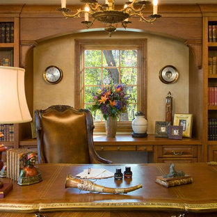 Example of a mid-sized ornate freestanding desk medium tone wood floor study room design in Minneapolis with beige walls, a standard fireplace and a stone fireplace