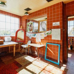Cette image montre un bureau atelier rustique de taille moyenne avec un mur rouge, un sol en carreau de terre cuite, aucune cheminée, un bureau indépendant et un sol rouge.
