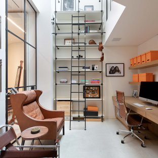 This is an example of a contemporary home office in London with white walls, a built-in desk and grey floors.