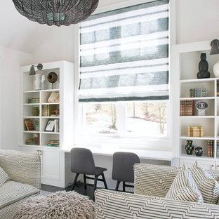 ニューヨークの中サイズのビーチスタイルのおしゃれなホームオフィス・書斎 (ベージュの壁、濃色無垢フローリング、吊り下げ式暖炉、造り付け机、茶色い床) の写真