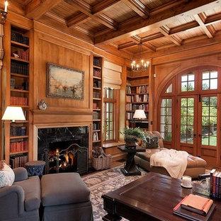Geräumiges Mediterranes Arbeitszimmer mit Arbeitsplatz, brauner Wandfarbe, braunem Holzboden, Kamin und freistehendem Schreibtisch in Santa Barbara