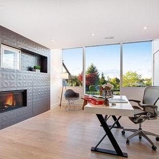 Idéer för ett stort modernt hemmabibliotek, med grå väggar, mörkt trägolv, en standard öppen spis, en spiselkrans i trä, ett fristående skrivbord och brunt golv