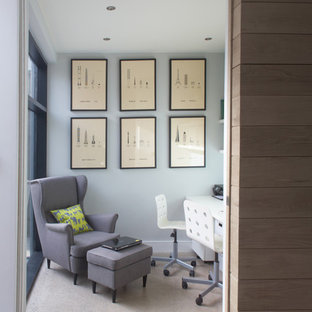 Inspiration for a contemporary home office and library in Dublin with concrete flooring, a built-in desk and grey walls.
