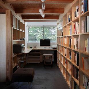 東京都下のコンテンポラリースタイルのおしゃれなホームオフィス・仕事部屋 (白い壁、造り付け机、黒い床) の写真