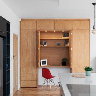Inredning av ett modernt litet hemmabibliotek, med vita väggar, ljust trägolv, ett inbyggt skrivbord och beiget golv