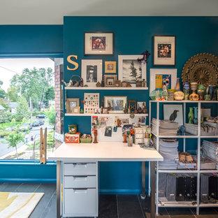 Bild på ett litet funkis arbetsrum, med blå väggar, skiffergolv, ett fristående skrivbord och grått golv