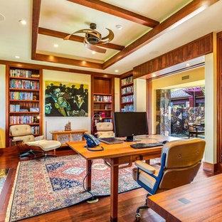 Immagine di una stanza da lavoro american style di medie dimensioni con pareti gialle, parquet scuro, camino classico, scrivania incassata e cornice del camino in pietra