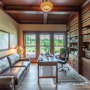 Bild på ett litet amerikanskt arbetsrum, med ett bibliotek, beige väggar, ljust trägolv, ett fristående skrivbord och gult golv