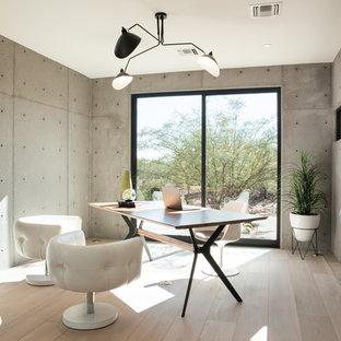 Esempio di un ufficio moderno di medie dimensioni con parquet chiaro, camino bifacciale, cornice del camino in cemento e scrivania autoportante
