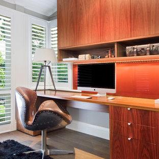 Diseño de despacho actual, de tamaño medio, sin chimenea, con suelo de madera oscura y escritorio empotrado
