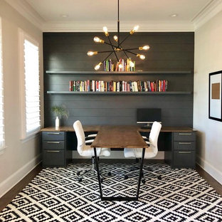 Trendy built-in desk dark wood floor and brown floor study room photo in Charlotte with gray walls