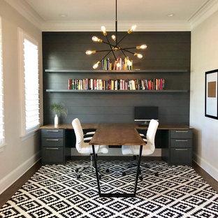 Ejemplo de despacho actual con paredes grises, suelo de madera oscura, escritorio empotrado y suelo marrón