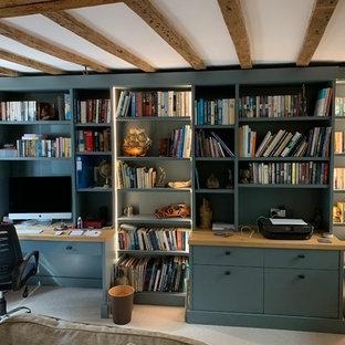 サセックスの広いコンテンポラリースタイルのおしゃれな書斎 (ベージュの壁、カーペット敷き、吊り下げ式暖炉、レンガの暖炉まわり、造り付け机、ベージュの床) の写真