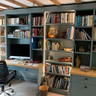 Inredning av ett modernt stort hemmabibliotek, med beige väggar, heltäckningsmatta, en hängande öppen spis, en spiselkrans i tegelsten, ett inbyggt skrivbord och beiget golv
