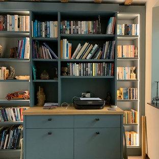 Exempel på ett stort modernt hemmabibliotek, med beige väggar, heltäckningsmatta, en hängande öppen spis, en spiselkrans i tegelsten, ett inbyggt skrivbord och beiget golv