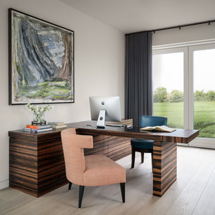 Medium sized contemporary study in Other with white walls, light hardwood flooring, a built-in desk and beige floors.