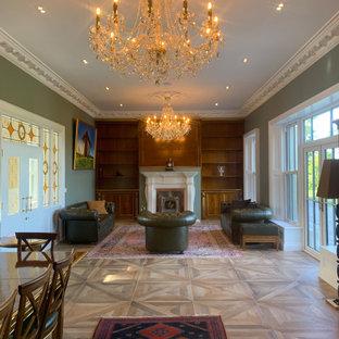 巨大なカントリー風おしゃれなホームオフィス・書斎 (ライブラリー、緑の壁、磁器タイルの床、横長型暖炉、石材の暖炉まわり、造り付け机、茶色い床、格子天井) の写真