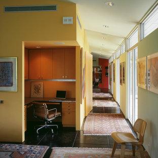 オースティンのミッドセンチュリースタイルのおしゃれなホームオフィス・仕事部屋 (黄色い壁、黒い床) の写真