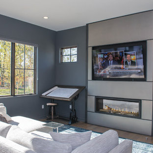 Photo of a large home studio in Cincinnati with grey walls, medium hardwood flooring, a ribbon fireplace, a metal fireplace surround, a freestanding desk and brown floors.