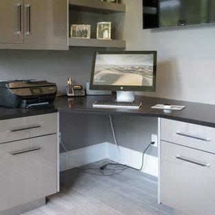 Foto di un piccolo studio minimal con pareti grigie, pavimento in gres porcellanato, pavimento marrone e scrivania incassata