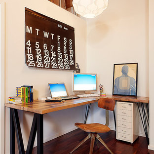 Urban freestanding desk dark wood floor study room photo in Los Angeles with white walls