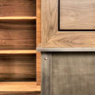 ニューヨークの広いカントリー風おしゃれな書斎 (茶色い壁、無垢フローリング、標準型暖炉、金属の暖炉まわり、造り付け机、茶色い床) の写真