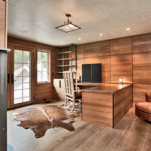 Inspiration for a large modern home office in New York with brown walls, medium hardwood flooring, a standard fireplace, a metal fireplace surround, a built-in desk and brown floors.