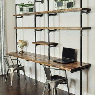 Exempel på ett litet industriellt hemmabibliotek, med grå väggar, mörkt trägolv, ett inbyggt skrivbord och brunt golv