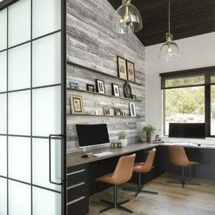 Inspiration för stora industriella hemmastudior, med vita väggar, ljust trägolv, ett inbyggt skrivbord och brunt golv