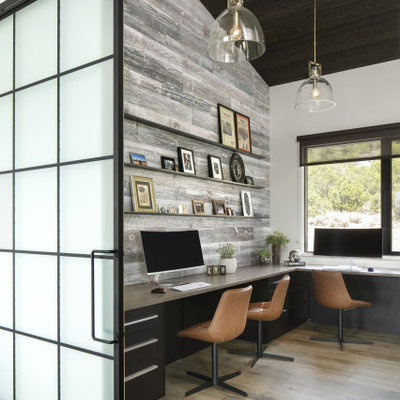 Inspiration for a large industrial built-in desk light wood floor, brown floor, vaulted ceiling and wood wall home studio remodel in Denver with white walls
