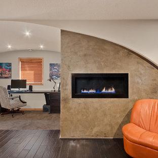 Modelo de despacho actual, de tamaño medio, con paredes blancas, suelo de madera oscura, chimenea lineal, marco de chimenea de hormigón, escritorio independiente y suelo marrón