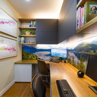 Idéer för ett mellanstort modernt hemmabibliotek, med mellanmörkt trägolv, ett inbyggt skrivbord och brunt golv