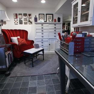 Foto di un ampio atelier industriale con pareti bianche, pavimento in cemento, nessun camino e scrivania autoportante