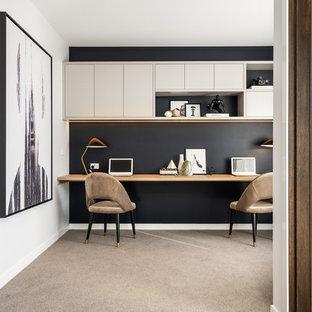 メルボルンのコンテンポラリースタイルのおしゃれなホームオフィス・仕事部屋 (黒い壁、カーペット敷き、造り付け机、ベージュの床) の写真