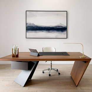 Photo of a modern study in Other with white walls, light hardwood flooring, a freestanding desk and beige floors.