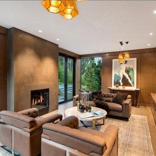Ejemplo de despacho actual, grande, con paredes marrones, todas las chimeneas, suelo marrón, suelo de madera en tonos medios y marco de chimenea de yeso