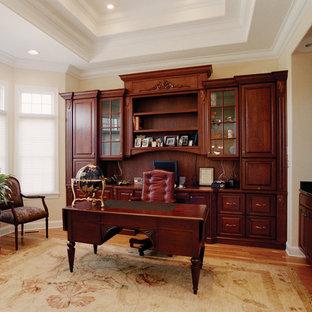 Пример оригинального дизайна: рабочее место среднего размера в классическом стиле с бежевыми стенами, паркетным полом среднего тона и отдельно стоящим рабочим столом без камина