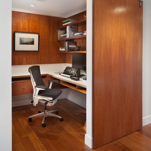 Inspiration for a contemporary home office and library in DC Metro with white walls, medium hardwood flooring, a built-in desk and brown floors.